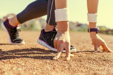 Sportswoman in running start position.