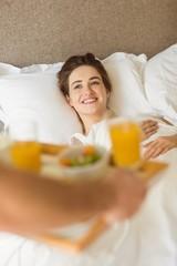 Cute couple having breakfast in bed