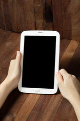 hand holding a tablet on wooden background