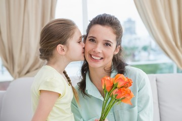Cute girl giving flowers to mother