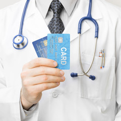 Doctor holding credit cards - 1 to 1 ratio
