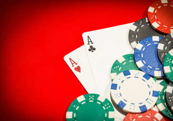 Pair of aces and chips on a red table