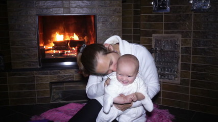 mother sitting with her baby near the fireplace at Christmas