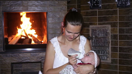 mother feeds her baby near the fireplace