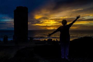 Junge Frau freut sich im Sonnenuntergang