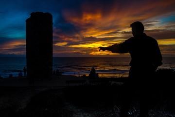 Silhouetten von Turm und Mann im Sonnenuntergang