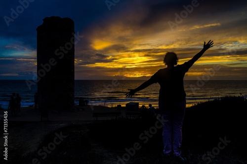 canvas print picture Junge Frau freut sich im Sonnenuntergang