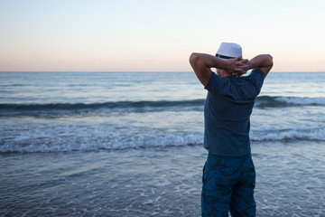 Человек смотрит на закат над морем в конце успешного дня.