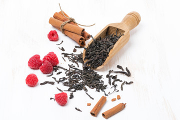 Dried tea leaves, cinnamon and fresh raspberries on white table