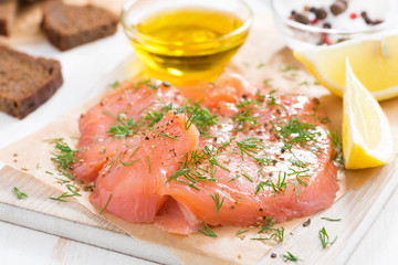 salted salmon, bread and ingredients on a wooden board, close-up