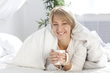 beautiful girl in the morning in bed with cup