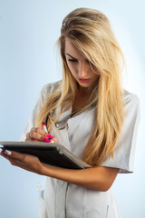 Vertical photo of young adult nurse with blonde hair writes