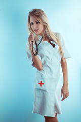 Sweet blonde nurse with stethoscope in white medical gown