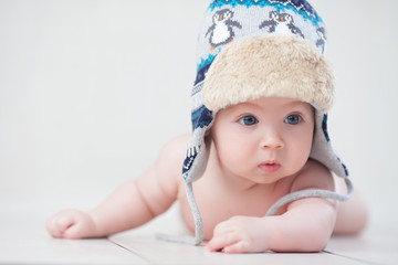 Baby in winter hat lying on the floor