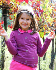 pretty little girl in the vineyard in autumn