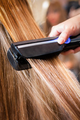 Woman at the beauty salon straightening hair