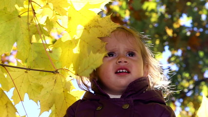 Baby playing with yellow leaves.