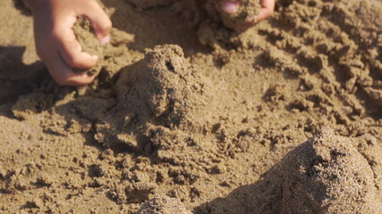 Little girl builds sand castle by himself on the beach.
