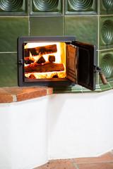 Kacheloffen mit brennendem Holzstapel