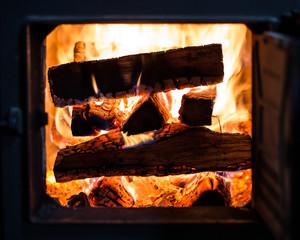 Ein brennender Stapel Holz im Kachelofen
