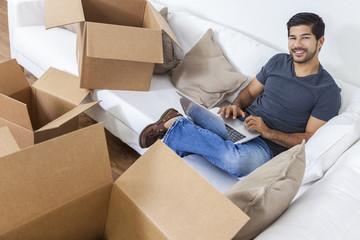 Asian Man Using Laptop Unpacking Boxes Moving House