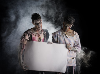 Two male zombies holding empty white banner