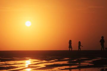 夕陽の海岸を散歩する親子のシルエット