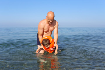 father teaching his son to swim in sea