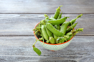 pods of green peas in a bowl