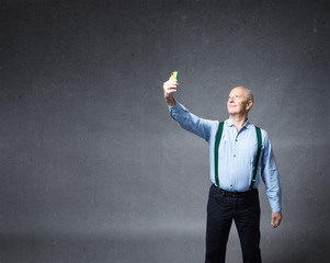 senior male taking selfie with phone