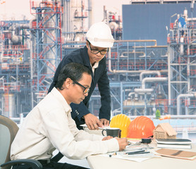 two engineer working on table against exterior of oil refinery p