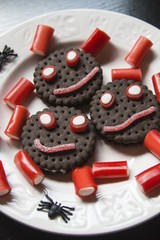 Smiling cookies with candies and pumpkins in Halloween festiviti