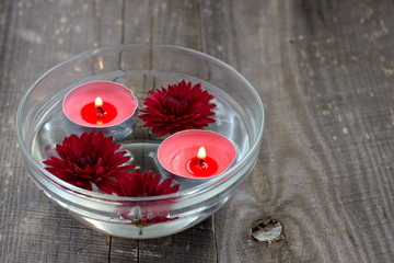 Red candles and flowers in a bowl
