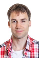 Passfoto eines lächelnden jungen Mannes im karierten Hemd
