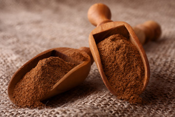 ground cinnamon spice powder in wooden spoon