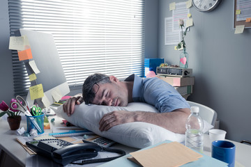 Exhausted businessman sleeping at workplace