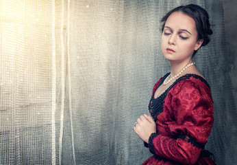 Sad beautiful woman in medieval dress near window