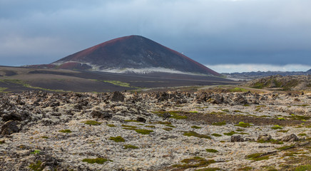 Icelandic volcano, lava fields and cloudy sky at sunset
