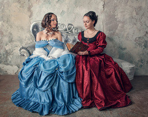 Two beautiful women in medieval dresses on the sofa reading book