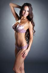 Smiling sexy underwear model posing at camera