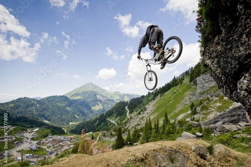 Mountainbiker jumping from a rock