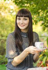 Девушка отдыхает в саду, с чашкой чая