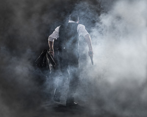 going to work,businessman walking in the haze , gun and bag