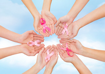close up of hands with cancer awareness symbol