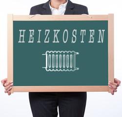 Frau hält Tafel mit dem Wort Heizkosten und dem Symbol Heizung