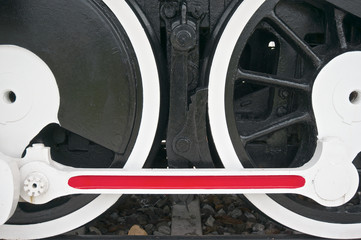 Black wheel of train with white and red mechanism