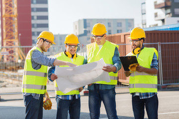 group of builders with tablet pc and blueprint