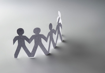 White paper people standing in a cycle and one orange paper man