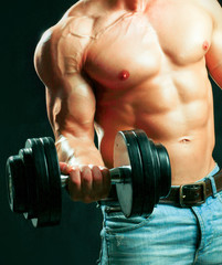 Unknown muscular man working out with dumbbells over black
