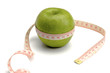 A green apple and a measuring tape, isolated on white background